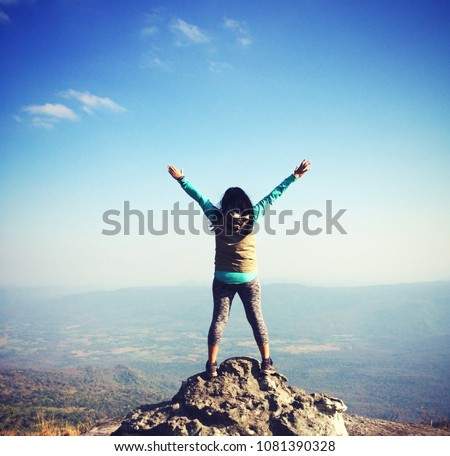 The woman standing on the top of mountain