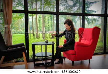 The woman that sits on armchair drinks tea, recreational and recreational idea #1521003620
