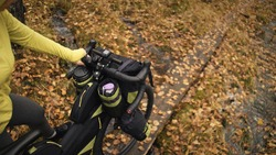 The woman travel on mixed terrain cycle touring with bikepacking. The traveler journey with bicycle bags. Sportswear in green black colors. The trip in magical autumn forest. Wooden bridge, river.