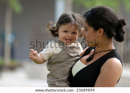The woman walk with a child in a park.