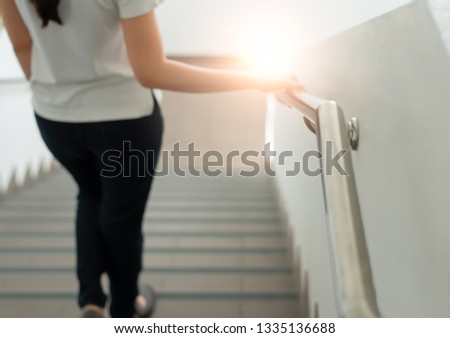 The woman walked, holding the railing, walking up and down the building for safety in balance during the steps up and down the stairs. In order to prevent accidents that may occur when being alone.