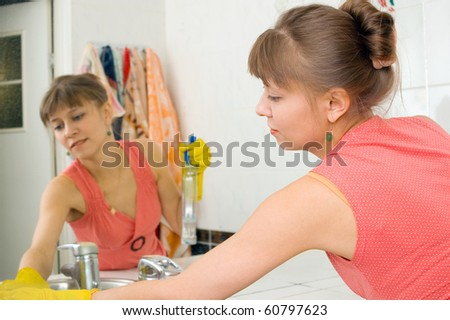 The woman washes a mirror in a bathroom