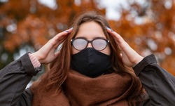 The woman wears a black mask due to the pandemic, but her glasses are fogged up. The problem of fogging glasses due to wearing a surgical mask.