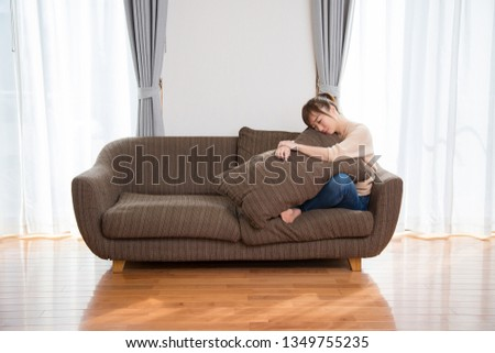 The woman who sits down on a sofa #1349755235
