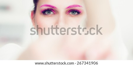 The woman with a bright pink make-up and pink eyebrows hides the face in hands. Studio portrait.