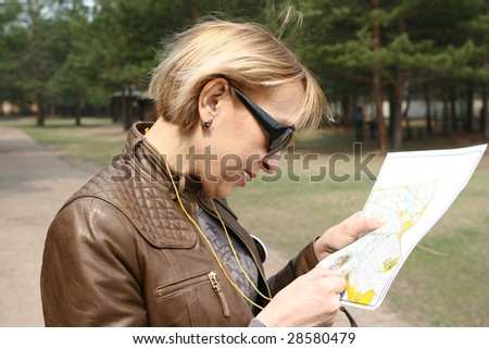 The woman with a compass studies a map sports orientation