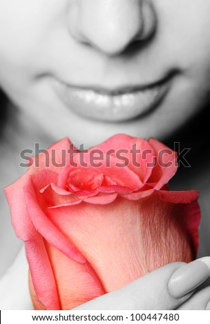 The woman with a rose close up. The monochrome image of the woman and a color rose