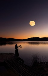 The woman with latern looked at the full moon.