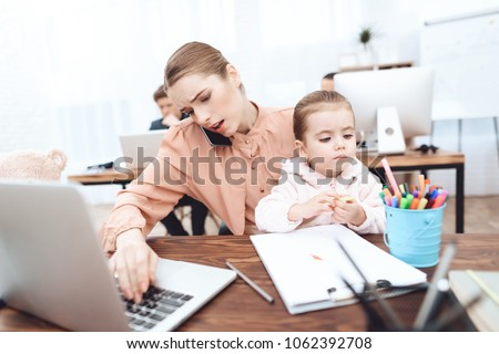 The woman with the child came to work. She works with her daughter in her arms. This is a business office. #1062392708