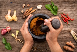 The Women hold pestle with mortar and spice paste of thai popular food red curry  on rustic wooden background. Spices ingredients chilli ,pepper, garlic,galanga lemongrass and Kaffir lime leaves .