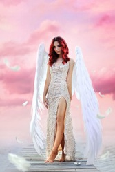 The wonderful angel landed on a coastal pier. This beautiful red-haired girl in a gold dress and with big wings. On the background of a beautiful pink sunset