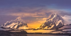 The wonderful fairy tale mountain landscape. The snow-covered Antarctic mountain crests on the sunrise sunset colorful background. Stunning panoramic view. Spectacular golden blue color combination.