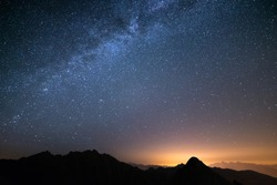 The wonderful starry sky on Christmas time and the majestic high mountain range of the Italian Alps, with glowing villages below.