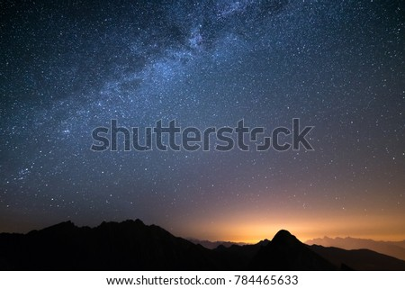 Shutterstock The wonderful starry sky on Christmas time and the majestic high mountain range of the Italian Alps, with glowing villages below.