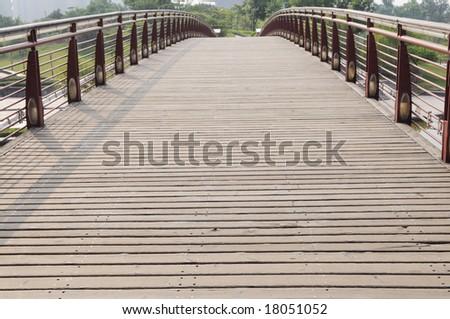 The wood bridge with wood planks and iron railings.