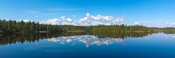 the wood lake in silent summer day with reflections of clouds