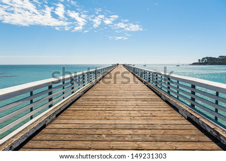 The wood pier on the sea under the blue sky