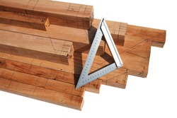 The wood sawn into a cuboid is painted with black lines and a triangular metal ruler is placed on it