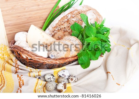 The wooden basket with mushrooms, bread, cheese, mint, quail eggs, and green onions