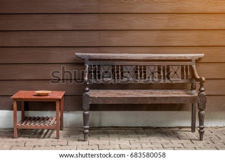 The wooden bench on the brick floor with the small ashtray on the square surface table with the flare from the edge , all brown photo color theme as vintage style.