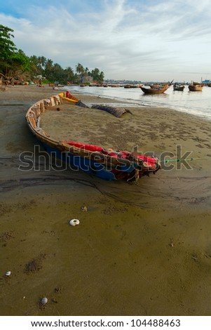 the wooden boat on a beach at a sunset