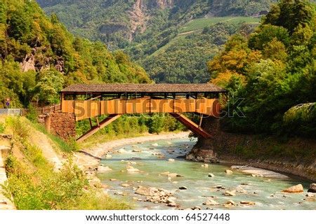 The Wooden Bridge Over the Adige River at the Foot of the Italian Alps