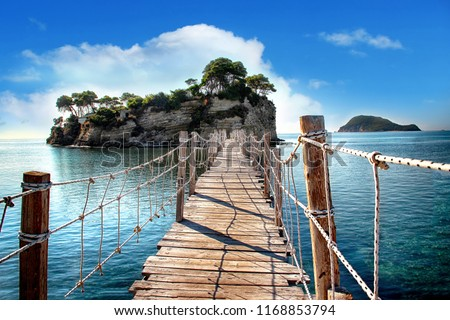 The wooden bridge overlooking the sea leads to an island with palm trees. It's a rope bridge. It is located in Zakynthos, Greece. #1168853794