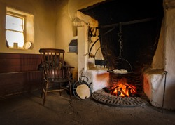 The wooden chair in the old style antique vintage kitchen with tools and fireplace for cooking