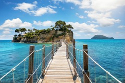 The wooden footbridge leading to the small island of Agios Sostis on Zakynthos, Greece, during a sunny summer day
