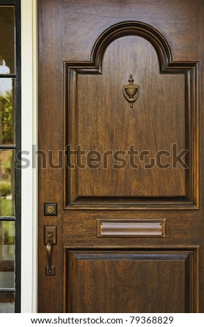 The wooden front door of a home with glass panel to the side. The glass is reflecting the homes opposite the door. Vertical shot.