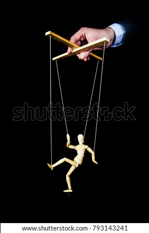 The wooden man on a string on black background. A puppeteer controls a puppet. Walking doll. #793143241