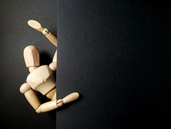 The wooden mannequin peeking out behind wall on dark background.copy space.