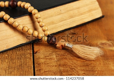 the Wooden rosary beads and holy bible on wooden background close-up