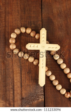 the Wooden rosary beads on wooden background close-up