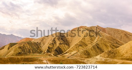 The wooden stairway on the edge of a small mountain in a blur background of mountain range from afar, in the Zhangye Danxia Geological Park, the World Heritage Site, in Gansu, China - Shutterstock ID 723823714