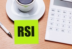 The wooden table has a white cup of coffee, a pen, a white calculator, and a green sticker with the text RSI Relative Strength Index. Business concept