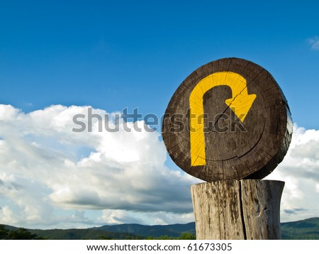The wooden U turn sign on the top of the hill