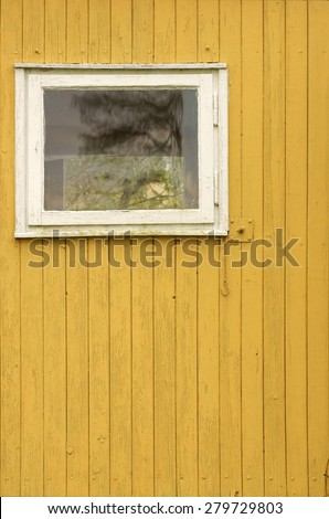 The wooden wall of a garden shed with a window / Wooden wall with window