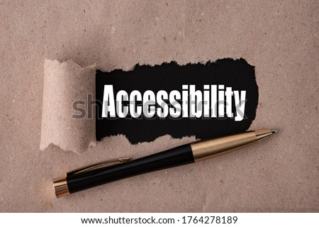 The word Accessibility is written under tear paper on a black background with a pen Foto stock ©