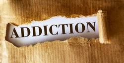 The word Addiction is written underneath brown torn paper.