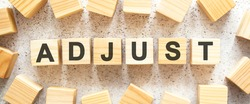 The word ADJUST consists of wooden cubes with letters, top view on a light background. Work space.