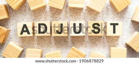 The word ADJUST consists of wooden cubes with letters, top view on a light background. Work space. Foto stock ©