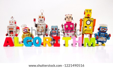 The word ALGORITHM  with wooden letters and retro robot toys on white