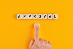 The word approval written on wood blocks with a male hand pushing the button. Concept of approving in business or finance.