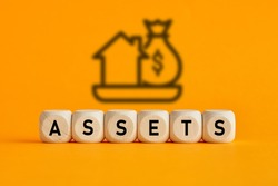 The word assets written on wooden cubes with assets icon on yellow background. Asset management or financial accounting concept.