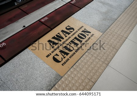 the word awas is malay language for caution. caution sign on the concrete platform at a train station. colour filter applied in post processing Zdjęcia stock ©