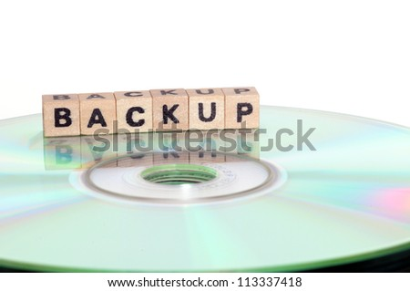 The word backup written in wooden letters standing on a computer-CD
