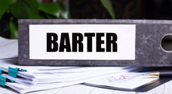 The word BARTER is written on a gray file folder next to documents. Business concept