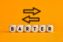 The word barter written on wooden cubes with exchange icons on yellow background. Trade in business market concept.