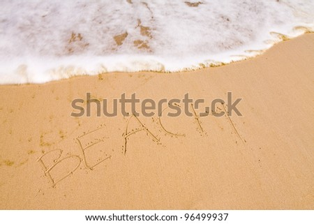 The word beach written with the finger in the sand, seashore